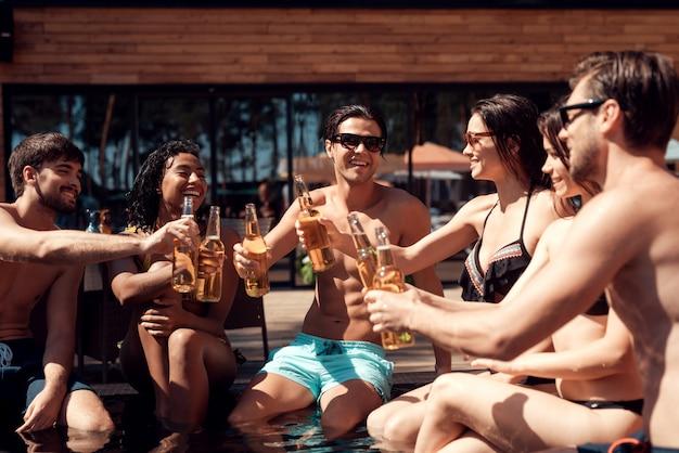 Jeunes gens souriants tenant des bouteilles de bière