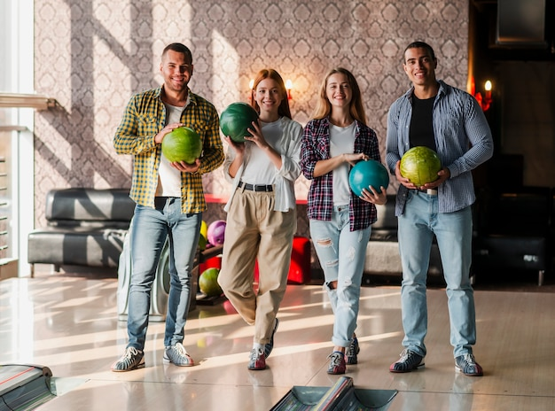 Jeunes gens tenant des boules de bowling colorés dans un club de bowling
