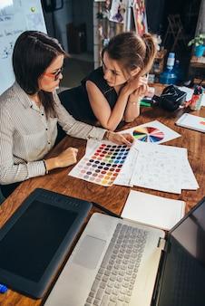Jeunes graphistes féminins assis au bureau avec ordinateur portable, nuanciers et quelques croquis discutant du nouveau projet en choisissant un concept.
