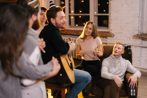 Des jeunes heureux chantent à la fête du nouvel an dans une maison confortable. heureux jeune homme joue de la guitare.