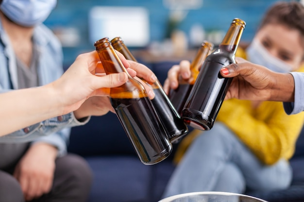 Des jeunes heureux et diversifiés s'amusant dans le salon, faisant tinter des bouteilles de bière racontant des histoires et des blagues pendant la pandémie mondiale. groupe multiethnique d'amis célébrant avec un toast lors d'une épidémie