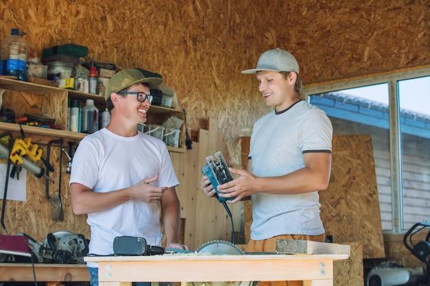 Jeunes hommes adultes, deux travailleurs travaillant dans un atelier de menuiserie avec des outils