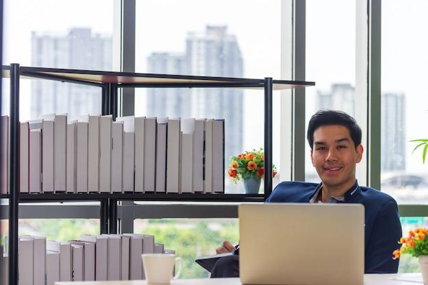 Jeunes hommes d'affaires asiatiques regardant le carnet de rendez-vous au bureau