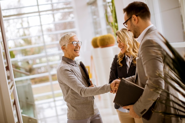 Jeunes hommes d'affaires avec des femmes d'affaires seniors et jeunes au bureau
