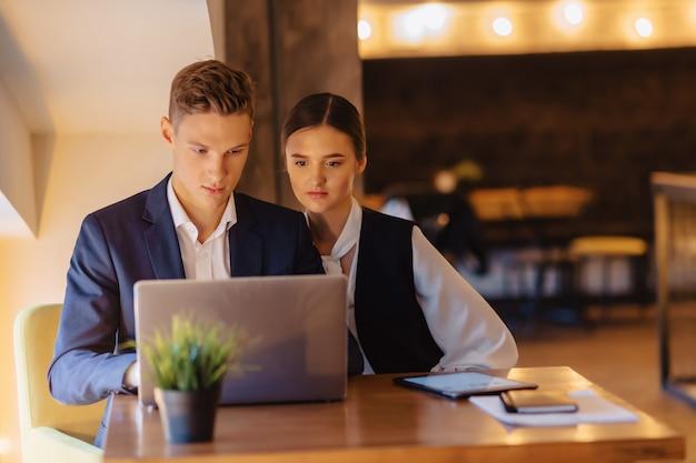 Jeunes hommes d'affaires, garçon et fille, travaillent avec un ordinateur portable, une tablette et des notes au café