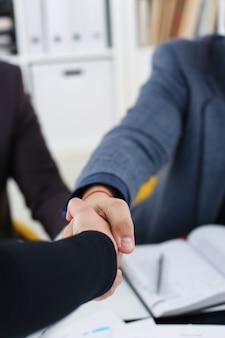 Jeunes hommes d'affaires heureux se sont réunis au bureau se serrent la main