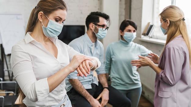 Jeunes hommes d'affaires lors d'une réunion avec des masques médicaux