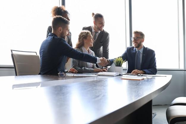 Jeunes hommes d'affaires modernes en tenue de soirée se serrant la main et souriant tout en travaillant au bureau.