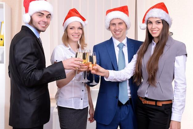 Jeunes hommes d'affaires prospères au bonnet de noel au bureau