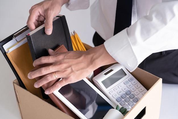 Les jeunes hommes d'affaires tristes licenciés détiennent des boîtes, y compris des plantes en pot et des documents pour le chômage des effets personnels, concept résigné.