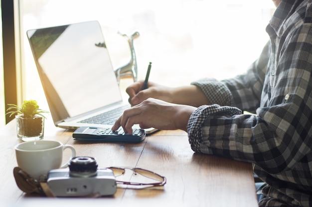 Jeunes hommes d'affaires utilisent une calculatrice à main, ordinateur portable placé sur un bureau près de la fenêtre
