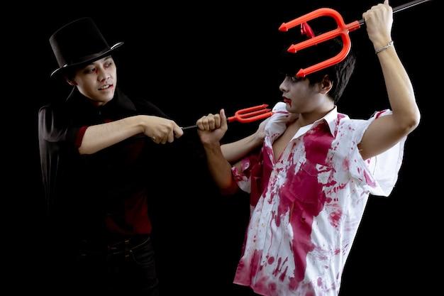 Jeunes hommes asiatiques en costume d'enfer, de mal et de sorcier avec combat sur fond noir avec concept pour le festival de la mode halloween en studio. deux adolescents asiatiques en cosplay halloween.