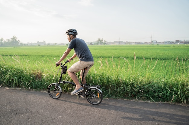 Les jeunes hommes asiatiques portent des casques pour faire du vélo pliant dans les rizières