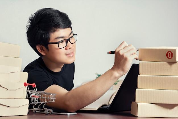 Jeunes hommes asiatiques style décontracté, entrepreneur vérifiant les articles en stock ou les boîtes d'emballage