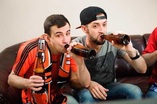 Les jeunes hommes boivent de la bière, mangent des chips et des racines pour le football.