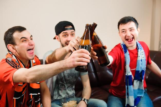 Les jeunes hommes boivent de la bière, mangent des chips et des racines pour le football