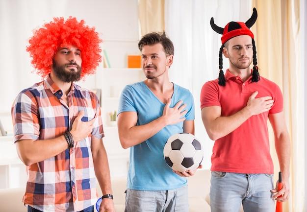 Les jeunes hommes boivent de la bière, mangent des pizzas et encouragent le football