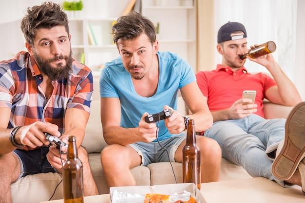 Jeunes hommes boivent de la bière, mangent des pizzas et jouent à des jeux