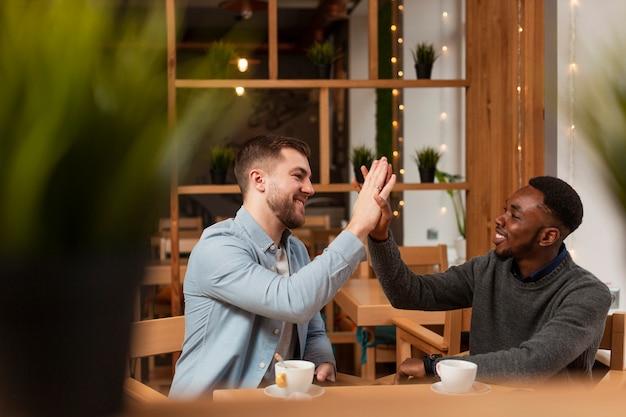 Jeunes hommes donnant cinq au restaurant