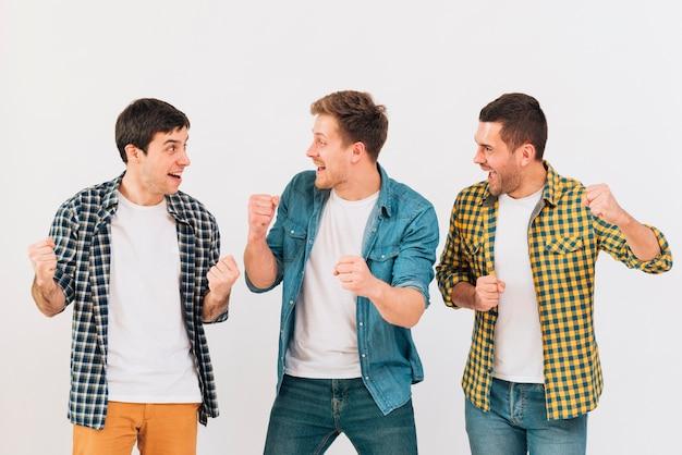 Jeunes hommes enthousiastes applaudissant et se moquant sur fond blanc