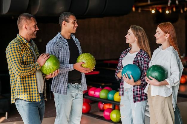 Jeunes hommes et femme debout dans un club de bowling