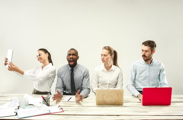 Jeunes hommes et femmes africains et caucasiens assis au bureau et travaillant sur des ordinateurs portables. l'entreprise, les émotions, l'équipe, le travail d'équipe, le lieu de travail, le leadership, le concept de réunion. différentes émotions de collègues