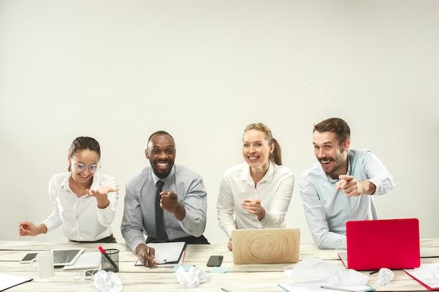 Jeunes hommes et femmes assis au bureau et travaillant sur des ordinateurs portables. concept d'émotions