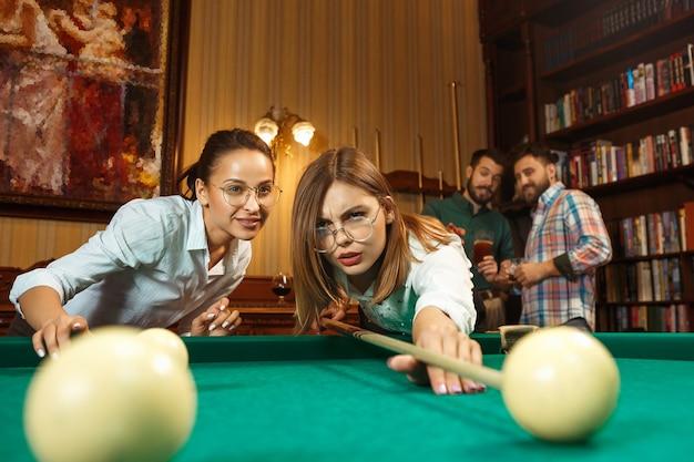 Jeunes hommes et femmes souriants jouant au billard au bureau ou à la maison après le travail. collègues de travail impliqués dans des activités récréatives. amitié, activité de loisirs, concept de jeu.