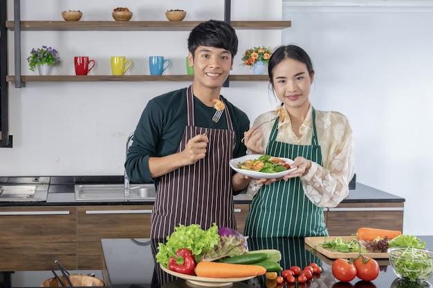 Des jeunes hommes et des filles asiatiques présentent une salade de crevettes