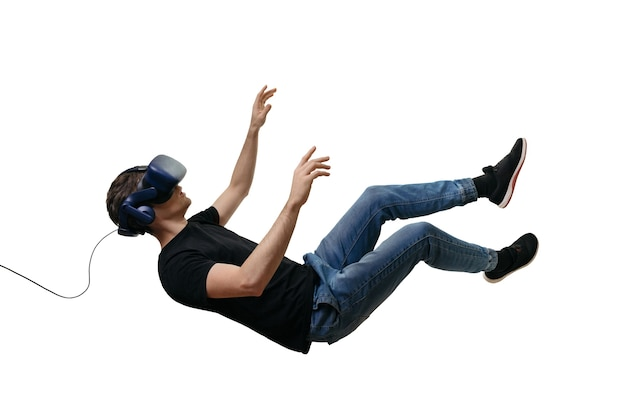 Jeunes hommes isolés tombant dans l'espace de gravité zéro tout en utilisant des lunettes de réalité virtuelle sur blanc
