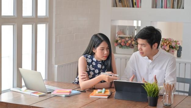 Les jeunes hommes et les jeunes femmes utilisent un ordinateur portable et aident à rédiger des rapports.