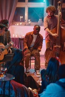 Jeunes hommes jouant dans une boîte de nuit pour les gens qu'ils chantent et jouent d'instruments de musique