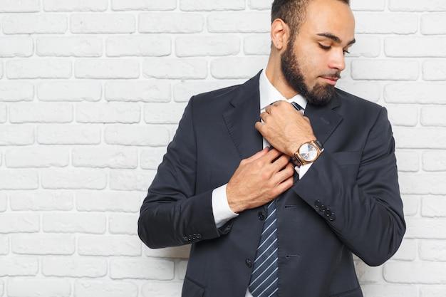 Jeunes hommes à la mode dans un costume contre le mur de briques