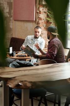 Jeunes hommes modernes assis à table dans un café vide et brainstorming sur des idées de séance photo ensemble