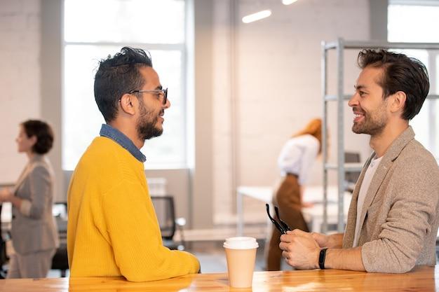 Jeunes hommes modernes positifs debout au comptoir dans un espace de bureau et discuter d'idées pour un projet en ligne pendant la pause-café