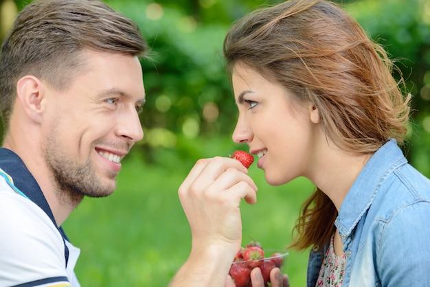 Jeunes hommes nourrir sa petite amie avec des fraises.