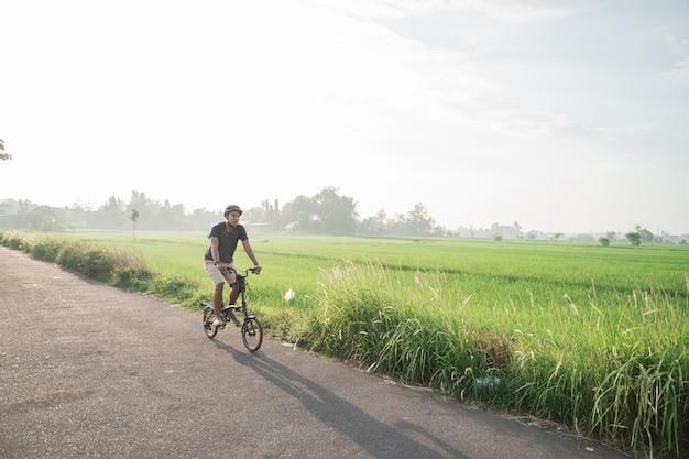 Les Jeunes Hommes Portent Des Casques Pour Faire Du Vélo Pliant Dans Les Rizières Photo Premium