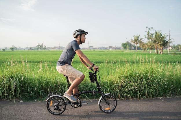 Les jeunes hommes portent des casques pour faire du vélo pliant dans les rizières