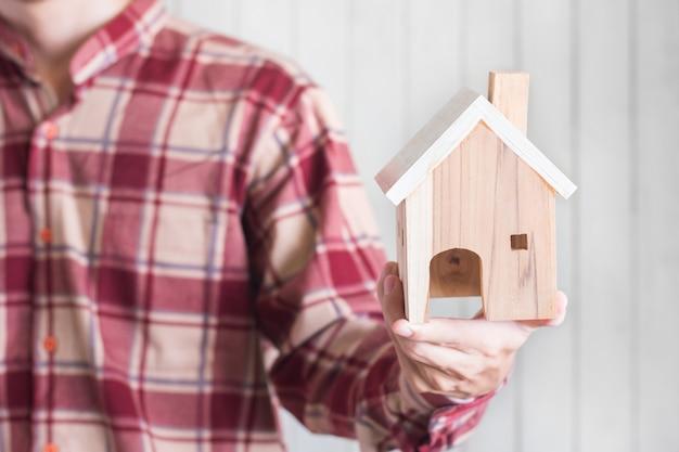 Jeunes hommes portent une chemise à carreaux rouges tenant un modèle de maison miniature, un concept d'investissement immobilier, une surface