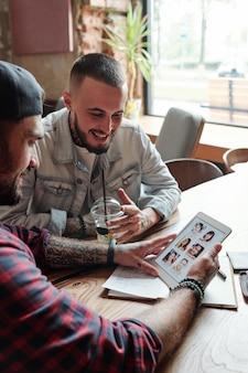 Jeunes hommes positifs assis à table dans un café et discuter des profils des femmes sur le site de rencontres à l'aide de la tablette