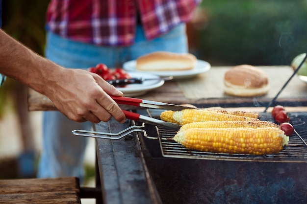 Jeunes hommes rôtir le barbecue sur le grill dans la campagne du chalet.