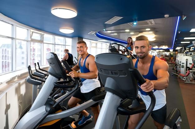 Jeunes hommes sportifs et femme exerçant sur des simulateurs dans une salle de sport