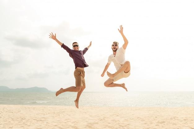 Jeunes hommes de tourisme joyeux énergique sautant à la plage
