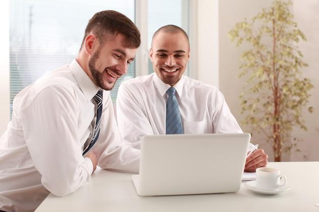 Jeunes hommes utilisant un ordinateur portable au bureau