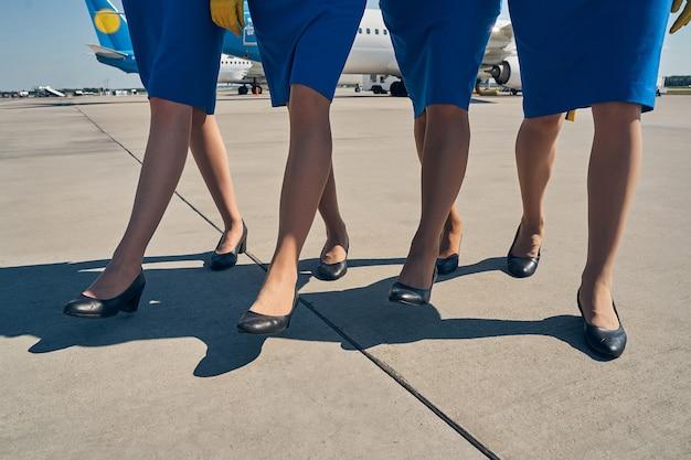 Jeunes hôtesses de l'air minces en jupes élégantes marchant à travers l'aérodrome