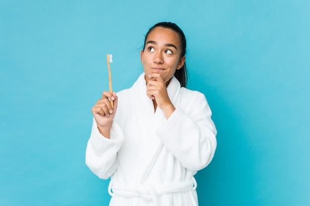 Les jeunes indiens métis tenant une brosse à dents à côté avec une expression douteuse et sceptique.