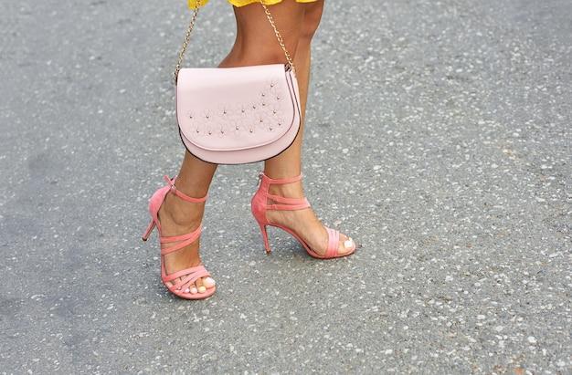 Jeunes jambes bronzées d'une fille en sandales à talons de couleur corail