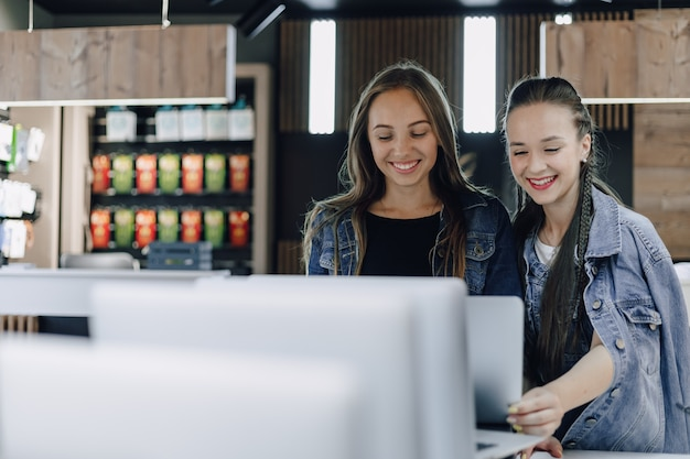 Jeunes jolies filles dans un magasin d'électronique utilisent un ordinateur portable lors d'une exposition