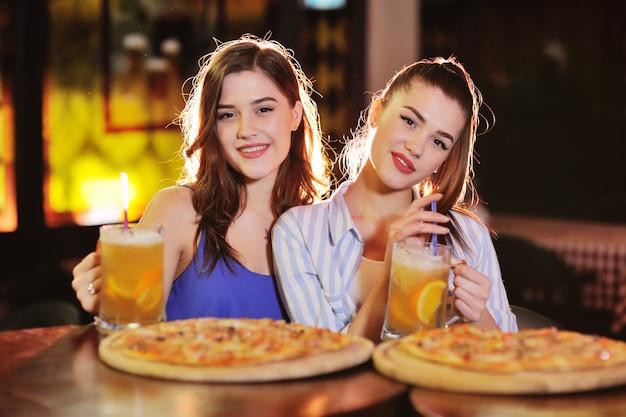 Jeunes jolies filles mangent une pizza et boivent de la bière ou un cocktail à la bière dans un bar ou une pizzeria