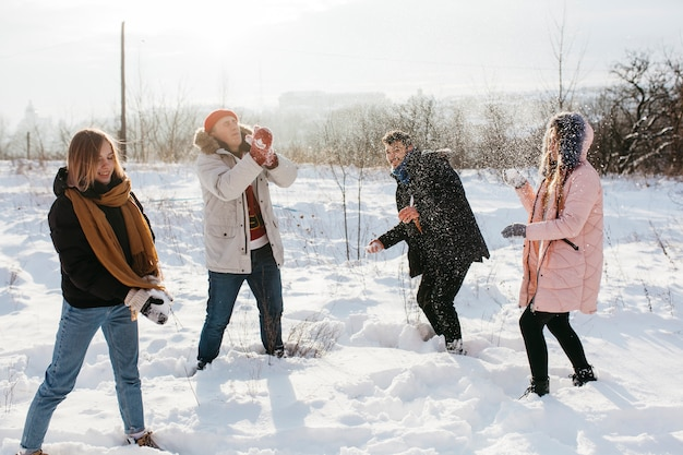 Jeunes jouant aux boules de neige en forêt d'hiver